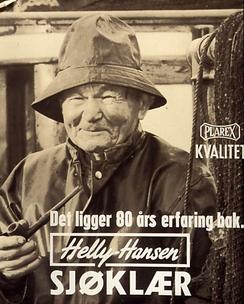I 1957 var plast et nytt pateriale brukt i tekstil, og forbrukerne måtte overbevises med henvisning til den lange erfaringen HH hadde med å lage solide plagg til de aller mest værutsatte brukerne - sjøfolk og fiskere. Var plast bre nok for dem ville det være bra nok for fritidstøy! Modellen var en ekte yrkesfisker - Karl Ludvig Hansen med sydvest og pipe i hånden.Foto: Repro Norsk Folkemuseum <br>