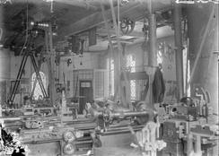 Verkstedinteriør som viser dreiebenker og andre verkstedmaskiner og drivsystemene med akslinger og reimer fra dampmaskinen ned til hver arbeidsmaskin.Foto: Norsk Teknisk Museum NTM T 242<br>