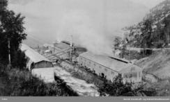 Legeringsverket i 1925 med transportband for råstoff over elva. På dette tidspunkt hadde Det Norske Zinkkompani A/S starta prøvedrift i anlegget. Foto: NVIM I-00687<br>