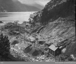 Utviding av Legeringsverket i 1915. Langs elva er stålkonstruksjonane til ein ny hall sett opp. I framgrunnen Sjoarfossen kraftstasjon, anleggsstasjonen frå 1907.Foto: NVIM I-TY0465<br>