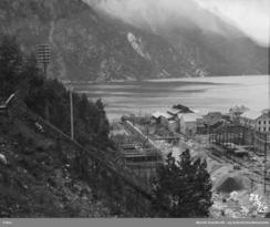 Legeringsverket i oktober 1915. Vi ser at det er sett opp køyrebru over Tysso og råstofflageret er under bygging på sørsida av elvaFoto: NVIM I-TY0462<br>