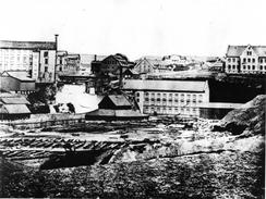 Tekstilfabrikkene Knud Graah og Hjula ligger på vestsiden av Akerselva. I øst er Glads mølle og bygninger som i dag er revet. Muligens er det et teglverk forgunnen. Bildet er trolig fra omkring 1880. Foto: NTM C 10050