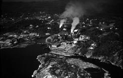 Fiskaa Verk før mye av dagens utbygging. Finerfabrikken Lumber sine sapellistokker ligger i forgrunden.Foto: Ukjent / Kristiansand kommune / IKAVA / DBVA.no<br>