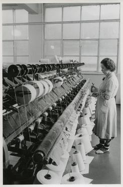 Kvinne ved spolemaskin på Trengereid Fabrikker, truleg 1950-52.Foto: Ukjend<br>