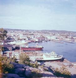 Kristiansand havn, Vesterhavna, sett fra utsiktspunktet ved Vesterveien. Lasteskip i tørrdokka på KMV, Kristiansand Mekaniske Verksted, Danskebåten,