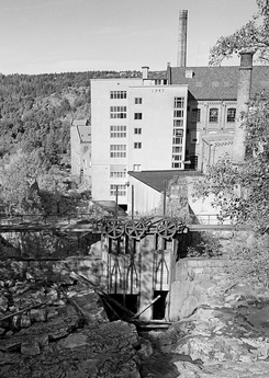 Deledammen ovenfor bomullsfabrikken i en tørrlagt periode hvor demningen syns fra innsiden. Her ser vi lukene som delte vannet mellom spinneriet og Saugbruksforeningen, som var den andre store brukeren av kraften fra Tistedalsfossen.Foto: Ljøstad / Norsk Skogmuseum<br>