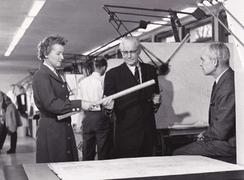 Dette bildet er et av de få vi har av Kværner Brugs mest berømte vannturbinveteraner, Henrik M.N. Christie (f. 1893-1968) og Torodd Sømming 1904-1967). Det er sekretær Gullborg Fjeldheim som overrekker Christie en tegning.Foto: Kværner Brugs Historiegruppe<br>