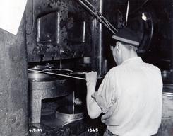 Gunnar Kristiansen stanser rondeller i 1954Foto: Aluminiumsmuseet / Vestfoldmuseene<br>